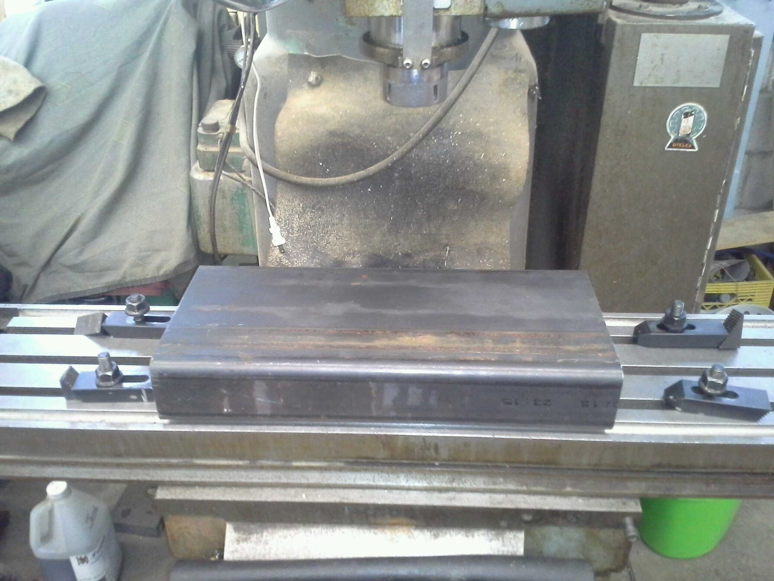 a raw piece of steel, unclamped on a milling machine